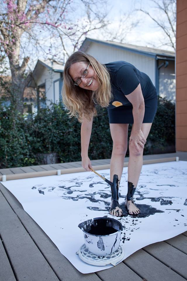 Artist Portrait of Jennifer Chenoweth painting with her feet with black paint for Austin Scene-Artists Portraits Künstlerportraits by Norman Hera
