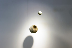 I Am The Cosmos, Eclipse Hemisphere sculpture, hanging from gallery wall