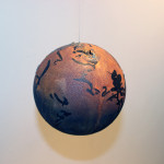 I Am The Cosmos, Ink on Rust Hemisphere sculpture, hanging from gallery wall