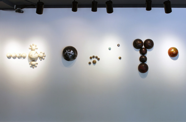 Straight on shot of Hemisphere sculptures hanging on gallery wall