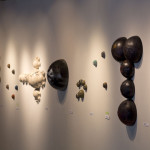 Side view of Hemisphere sculptures, hanging on gallery wall