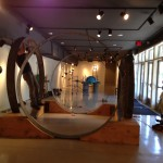 Man doing pull ups on North Gate sculpture, Sacred Space in stallation, Dougherty Arts Center