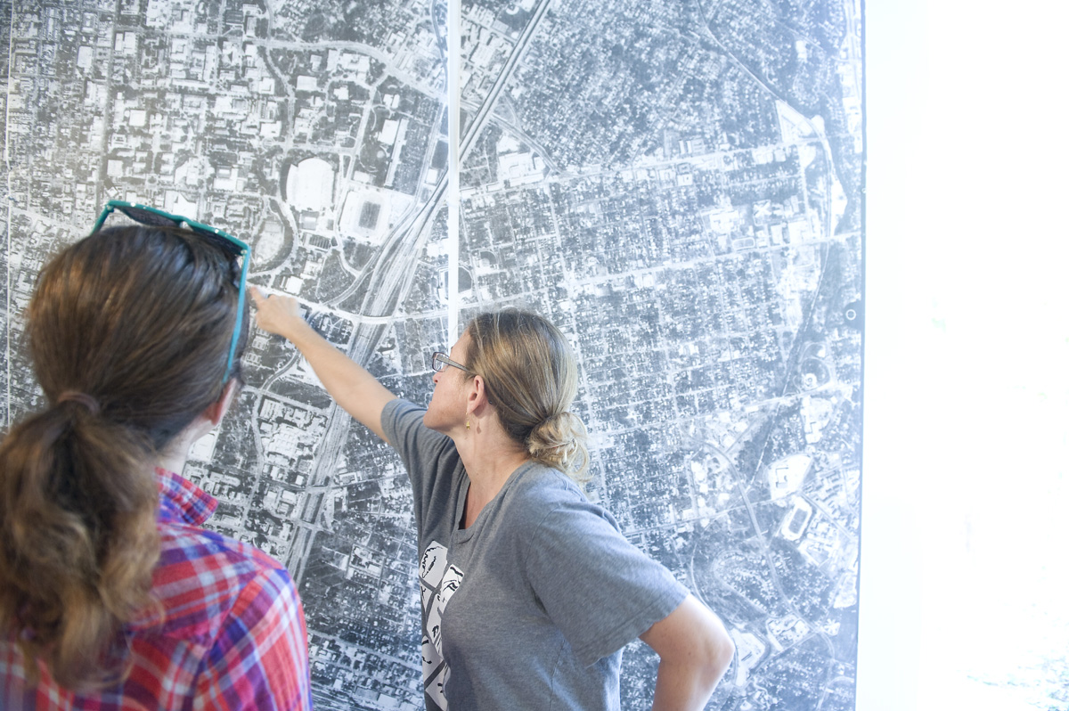 Jennifer pointing at specific place on aerial map of Austin, Hedonic Map Project installed at CoLab
