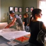 Andrea Pramuk selling art at Fisterra Studio, EAST 2011, by Judith Simonds
