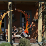 Jennifer and Stella seen through fire ring sculpture, EAST 2012 at Fisterra Studio by Philip Rogers