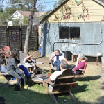 Friends sitting in backyard chatting, EAST 2012 at Fisterra Studio by Philip Rogers