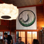 People conversing in dining room with circular painting and large lantern, EAST 2012 at Fisterra Studio by Dante Dominick