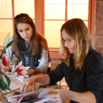 Liana Putrino and Jennifer Chenoweth looking at the EAST catalog, EAST 2012 at Fisterra Studio by Dante Dominick