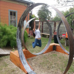 Person playing on circular sculpture, EAST 2013 at Fisterra Studio by Dante Dominick
