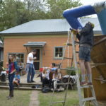Henry Pitre working on sculpture in yard